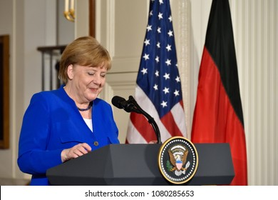 WASHINGTON, DC - APRIL 27, 2018: German Chancellor Angela Merkel smiles as she speaks at a joint press conference with President Trump in the East Room of the White House.