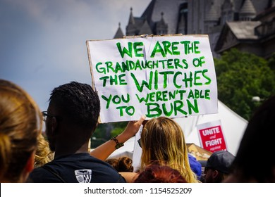 WASHINGTON, DC - AUGUST 13, 2018: An activist in DC holds a protest sign at the Unite the Right 2 counter protest