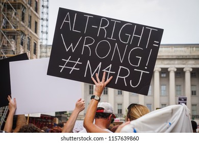 "WASHINGTON, DC - AUGUST 13, 2018: An activist in DC holds a protest sign that says ""Alt-right = Wrong"" at the Unite the Right 2 counter protest"