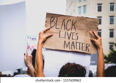 "WASHINGTON, DC - AUGUST 13, 2018: An activist in DC holds a protest sign that says ""black lives matter"" at the Unite the Right 2 counter protest"