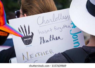 "WASHINGTON, DC - AUGUST 13, 2018: An activist in DC holds a protest sign that says ""Charlottesville hasn't forgotten Heather"" at the Unite the Right 2 counter protest"