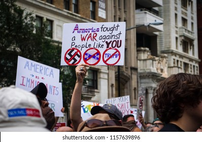 "WASHINGTON, DC - AUGUST 13, 2018: An activist in DC holds a protest sign that says ""America fought a war against people like you"" at the Unite the Right 2 counter protest"