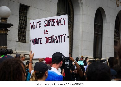 "WASHINGTON, DC - AUGUST 13, 2018: An activist in DC holds a protest sign that says ""white supremacy is white depravity"" at the Unite the Right 2 counter protest"