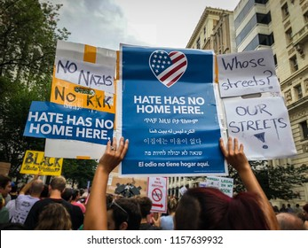 "WASHINGTON, DC - AUGUST 13, 2018: An activist in DC holds a protest sign that says ""Hate has no home here"" at the Unite the Right 2 counter protest"