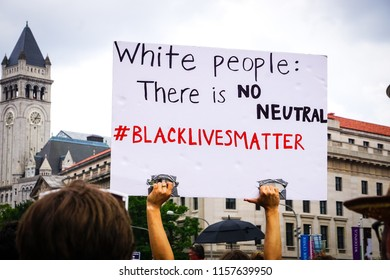 "WASHINGTON, DC - AUGUST 13, 2018: An activist in DC holds a protest sign that says ""There is no neutral"" at the Unite the Right 2 counter protest"