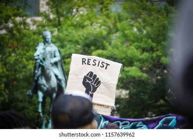 "WASHINGTON, DC - AUGUST 13, 2018: An activist in DC holds a protest sign that says ""Resist"" at the Unite the Right 2 counter protest"