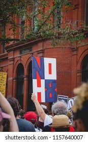 "WASHINGTON, DC - AUGUST 13, 2018: An activist in DC holds a protest sign that says ""No H8"" at the Unite the Right 2 counter protest"
