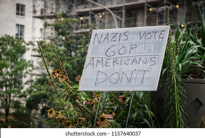 """WASHINGTON, DC - AUGUST 13, 2018: AA sign says """"Nazis vote GOP Americans don't"""" at the Unite the Right 2 counter protest"""