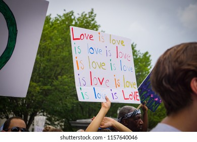 "WASHINGTON, DC - AUGUST 13, 2018: An activist in DC holds a protest sign that says ""love is love is love"" at the Unite the Right 2 counter protest"