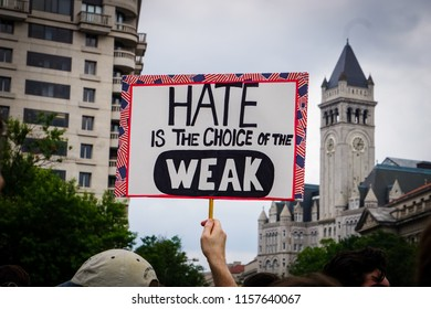 "WASHINGTON, DC - AUGUST 13, 2018: An activist in DC holds a protest sign that says ""Hate is the choice of the weak"" at the Unite the Right 2 counter protest"