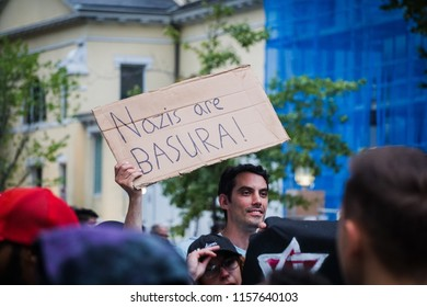 "WASHINGTON, DC - AUGUST 13, 2018: An activist in DC holds a protest sign that says ""Nazis are basura (trash)"" at the Unite the Right 2 counter protest"