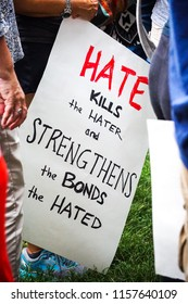 "WASHINGTON, DC - AUGUST 13, 2018: An activist in DC holds a protest sign that says ""Hate kills the hater"" at the Unite the Right 2 counter protest"