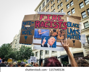 "WASHINGTON, DC - AUGUST 13, 2018: An activist in DC holds a protest sign that says ""Fire Racists"" at the Unite the Right 2 counter protest"
