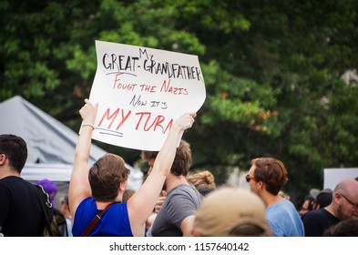 "WASHINGTON, DC - AUGUST 13, 2018: An activist in DC holds a protest sign that says ""Now it's my turn"" at the Unite the Right 2 counter protest"