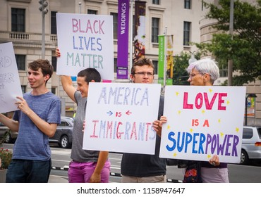 "WASHINGTON, DC - AUGUST 13, 2018: An activist in DC holds a protest sign that says ""Love is a superpower"" at the Unite the Right 2 counter protest"