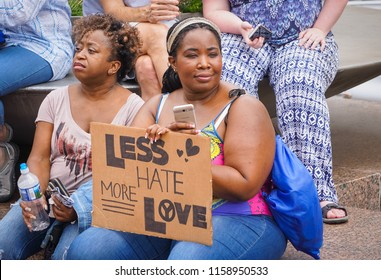 "WASHINGTON, DC - AUGUST 13, 2018: A woman in DC holds a protest sign that says ""Less Hate, More Love"" at the Unite the Right 2 counter protest"