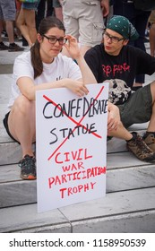 "WASHINGTON, DC - AUGUST 13, 2018: An activist in DC holds a protest sign that says ""Civil war paricipation trophy"" at the Unite the Right 2 counter protest"