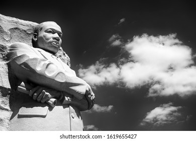 WASHINGTON DC - AUGUST, 2018: Dr Martin Luther King, Jr stands carved from white stone at the memorial in his name with arms crossed looking out into monochrome sky.