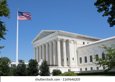 WASHINGTON, DC - AUGUST 23, 2018:  The United States flag flies in front of the Supreme Court Building on a beautiful summer day in Washington, DC.