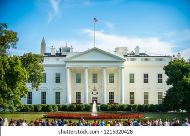 WASHINGTON DC - AUGUST 27, 2018: Crowds of tourists gather along the pedestrian walkway of Pennsylvania Avenue on a bright summer afternoon outside the grounds of the White House.