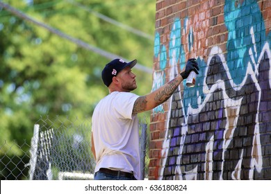 Washington, DC - August 7, 2016: Graffiti artists participate in a live mural painting at 1301 Rhode Island Avenue alongside live music and a vendor market.