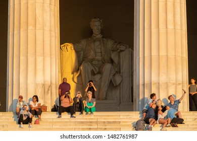 WASHINGTON DC - CIRCA AUGUST 2019: People sitting on steps of Lincoln Memorial at sunrise