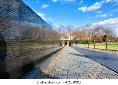 WASHINGTON DC - DECEMBER 19: Vietnam Veterans Memorial. The wall in black granite with the engraved names of Veterans. Alongside some visitors walking. Shot at December 19, 2015 in Washington DC, USA.