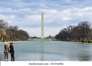WASHINGTON DC, DECEMBER 19: View of Washington Monument from Abraham Lincoln Memorial with two tourist girls. Taken in December 19 2015 in Washington DC, USA.