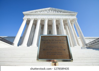 WASHINGTON, DC - DECEMBER 26, 2018: Welcome sign at the Supreme Court of the United States directs visitors to the side entrances. Despite the sign, multiple visitors attempt to enter via the steps.