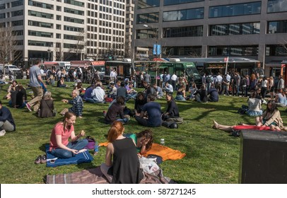 WASHINGTON DC - FEB 24, 2017:  With temperatures in upper 70's (F), lunchtime crowd soaks up the sun in Farragut Square, enjoying what meteorologists are saying will be the warmest February on record.
