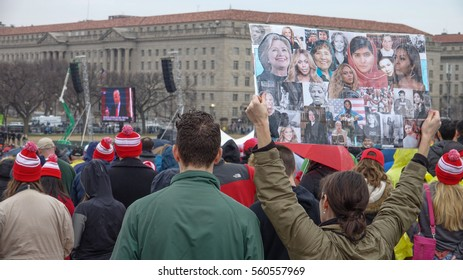 WASHINGTON, DC - JAN. 20, 2017: Inauguration of Donald Trump, protest sign foreground, Trump on jumbotron screen in distance; subdued, light crowd near Washington Monument watch.