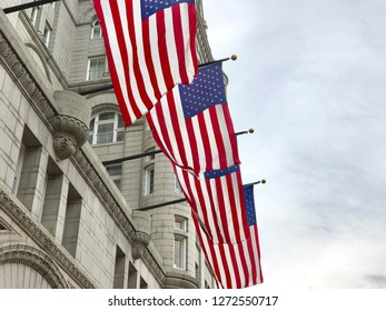WASHINGTON, DC - JANUARY 1, 2019: AMERICAN USA FLAGS at TRUMP INTERNATIONAL HOTEL with building facade. Trump Hotel is located in the Old Post Office building, a national historic site.