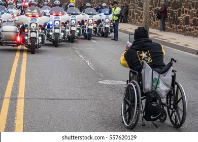 Washington, DC - January 16, 2017: Spectator in wheelchair snaps a photo of the police motorcycle escorts at the start of the Martin Luther King, Jr. Day Peace Walk and Parade.