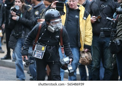 WASHINGTON DC - JANUARY 20 2017: Protests filled Washington DC during Donald Trump's Inauguration Day. Photojournalist in protective gear moves between lines