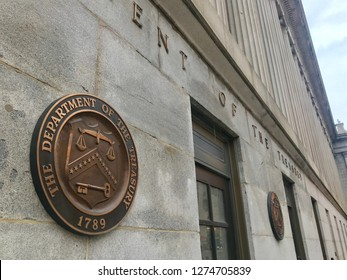 WASHINGTON, DC - JANUARY 4, 2019: TREASURY DEPARTMENT headquarters building entrance with sign and seal.