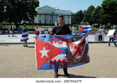 """Washington, DC – July 14, 2021: A man displays the Cuban flag with Che Guevara on it and a hand written message of """"No Mas"""" expressing that the Cuban people have had enough."""