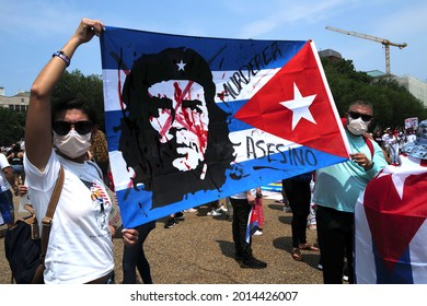 Washington, DC – July 25, 2021: A protester holds an anti-Che Guevara image imposed on a Cuban Flag at a rally.