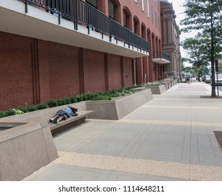 WASHINGTON, DC - JUNE 17, 2018: Homeless man sleeping on bench on 17th Street in front of the New Executive Office Building (US Government Offices), around the corner from the White House