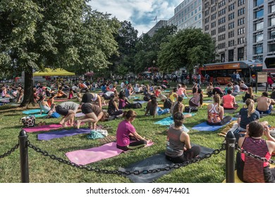 WASHINGTON, DC - JUNE 2017: Group yoga downtown DC after work; Yoga in the park, Farragut Park, weekly early evening May - Sept., sponsored by Golden Triangle downtown association.