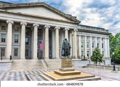 WASHINGTON, DC - JUNE 22, 2017 Albert Gallatin Statue US Flag US Treasury Department Washington DC.  Statue by James Fraser and dedicated in 1947.