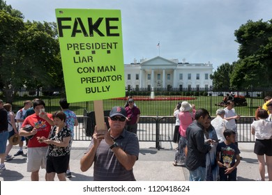 WASHINGTON, DC - JUNE 25, 2018; Protester at White House with placard characterizing President Trump's characteristics - con man, liar, predator, bully. Tourists nearby.