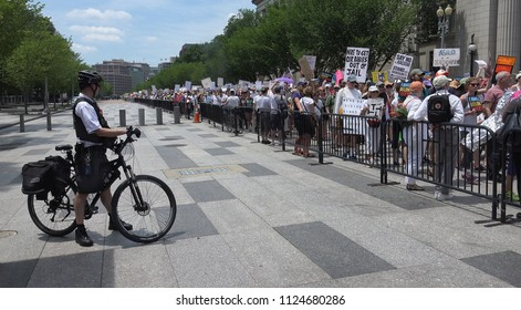 WASHINGTON, DC - JUNE 30, 2018: Protesting Trump's immigration policy & family detention and separation, thousands leave rally near White House to the Justice Department. Families Belong Together