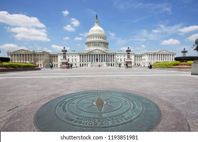 WASHINGTON, DC - JUNE 30, 2018:  The East point of a compass directs tourists to the Supreme Court Building and the Library of Congress, while the US Capitol can be seen in the background.