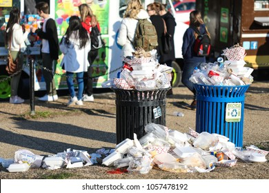Washington, DC - March 10, 2018: Although the trash cans on the National Mall are full, tourists continue to pile their garbage on top of them, creating a mess.