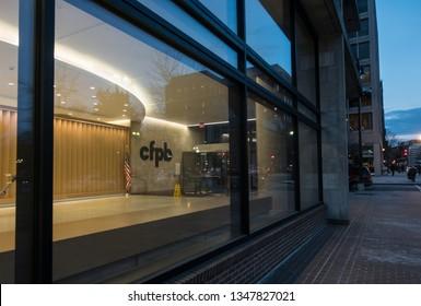 WASHINGTON, DC - MARCH 14, 2019: Consumer Financial Protection Bureau entrance, aka the CFPB at sunset. Note logo through lobby window. 17th Street downtown DC.