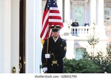 Washington, DC – March 17, 2017: A soldier holds an American flight outside the White House entrance as President Donald Trump awaits the arrival of German Chancellor Angela Merkel.