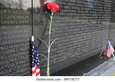 WASHINGTON, DC - MARCH 2016: Lone red carnation and American flag at Vietnam Veterans Memorial