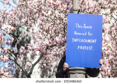 WASHINGTON, DC - March 24, 2018: During March for Our Lives DC, a nationwide protest against gun violence, a person holds an anti-Trump sign calling for the president's impeachment.