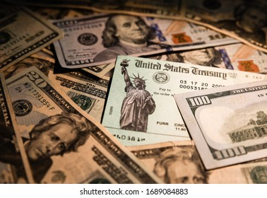 WASHINGTON DC - MARCH 30, 2020:  United States Treasury check surrounded by US currency.  Illustration for Government stimulus checks expected to ease impact of Coronavirus (Covid-19) restrictions.