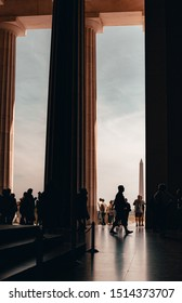Washington D.C., Maryland / United States - September 21, 2019: People walk in between the pillars of the Lincoln Memorial pillars with the Washington Monument standing tall in the back.